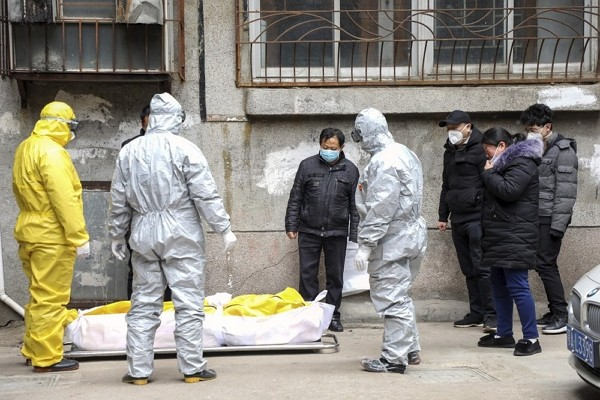Funeral home workers remove the body of a person suspected to have died from coronavirus from a residential building in Wuhan.