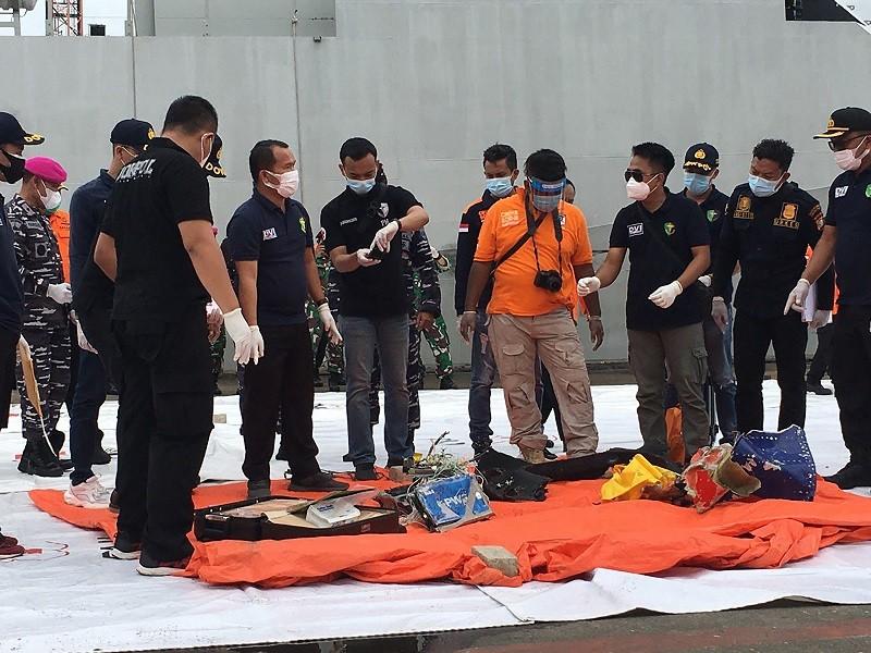 印尼搜救人員10日在雅加達國際貨櫃碼頭的搜救指揮中心, 檢視從海底尋獲, 疑似墜海班機的機身及乘客物品。中央社