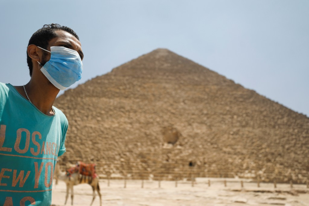 Man wearing face mask seen in front of Great Pyramids of Giza after it reopened for tourist visits. (Reuters photo)