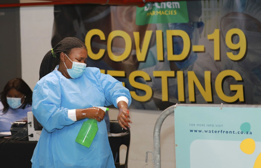 Healthcare worker sanitizes her hands before conducting COVID-19 tests atDis-Chem drive-through testing stationin Cape Town, South Africa....