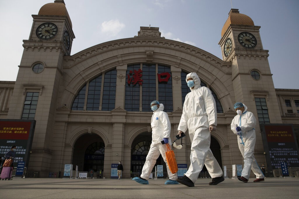 In this April 7, 2020, file photo, workers in protective suits walk past the Hankou railway station.