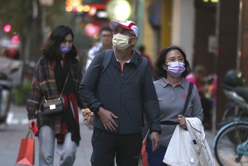 People wearing face masks to protect against the spread of the coronavirus walk in Taipei.