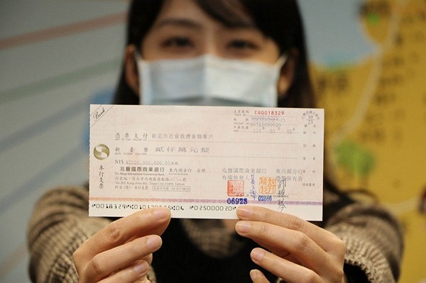 New Taipei Government employee displays check from anonymous donor. (New Taipei Social Welfare Department photo)