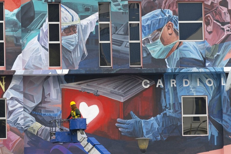 A worker adds finishing touches to mural tribute to frontline workers in the COVID-19 pandemic outside a hospital in Kuala Lumpur, Malaysia, Jan. 21, ...