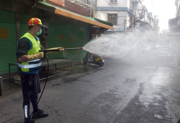 Worker spraying disinfectant in Taoyuan's Bade District.