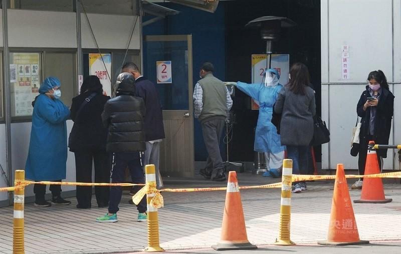 圖為桃園醫院醫護人員25日在醫院出入口外嚴陣以待。(中央社)