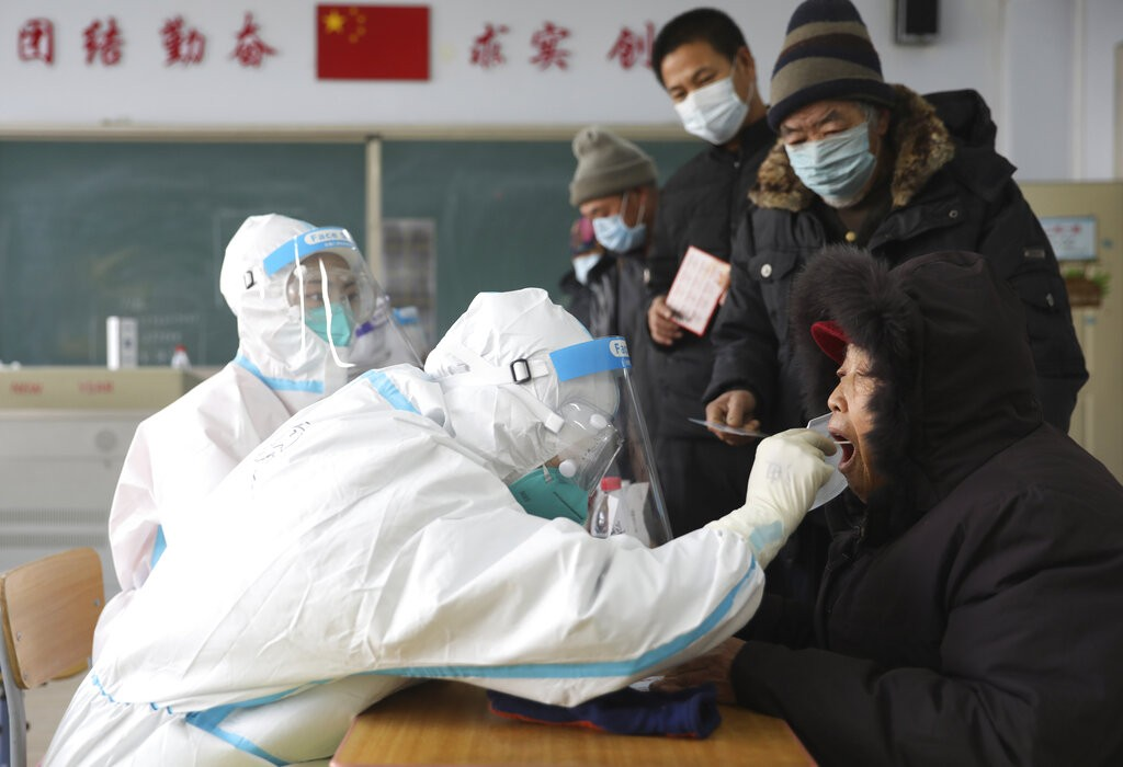 Workers in protective suits take swabs in Shenyang, Liaoning Province.