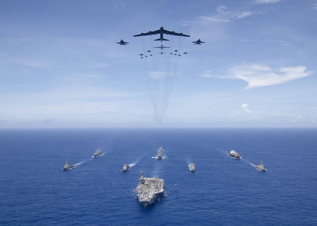 USS Ronald Reagan leads formation of Carrier Strike Group 5 ships as USAF B-52 bombers and U.S. Navy F/A-18 Hornets fly overhead.