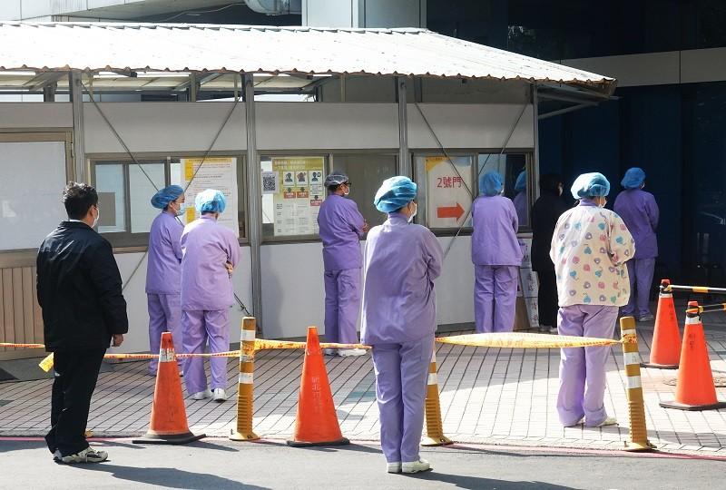 圖為1月29日桃園醫院戶外採檢區,醫護人員按照標準作業程序,保持安全距離準備進入醫院。(中央社檔案照片)