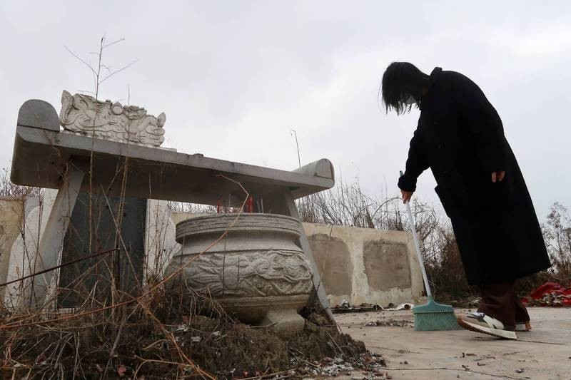 Woman sweeps tomb ofgrandmother and father who died of complications from coronavirusin Wuhan cemetery. (Reuters photo)