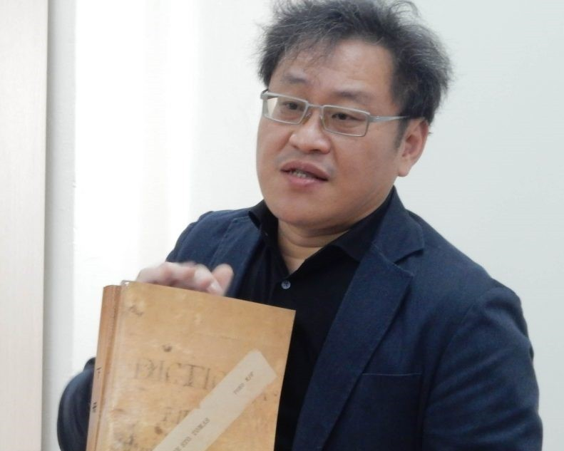 Dr. Fabio Yu-Chung Lee holding historic dictionary. (Philippine Daily Inquirer photo)
