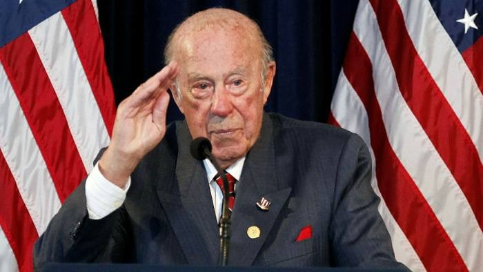 George Shultz salutes Ronald Reagan during the 20th anniversary of the fall of the Berlin Wall in 2009.