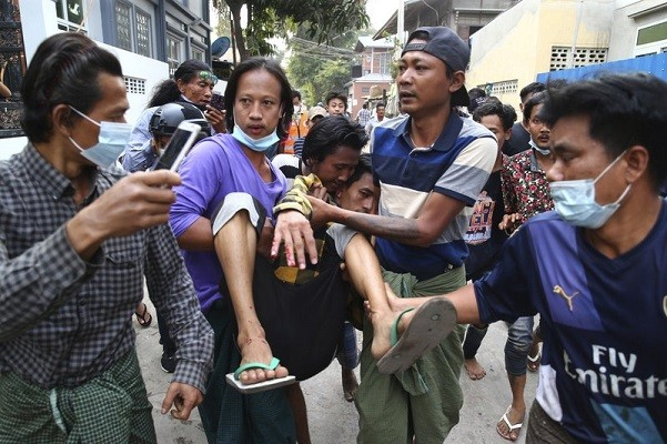 Man carried after police dispersed protesters in Mandalay, Myanmar, on Feb. 20, 2021.