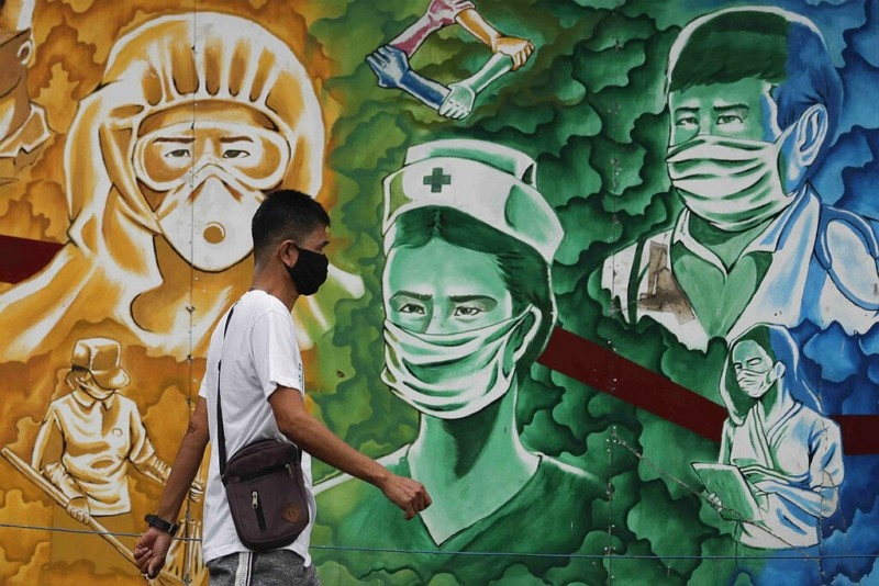 A man wearing a protective mask walks beside a mural of health workers outside the Mission Hospital in Pasig, Philippines.
