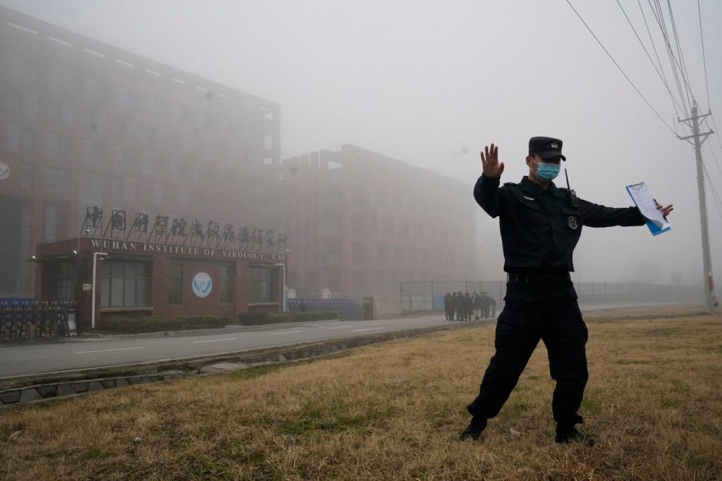 Security official moves journalists away from the Wuhan Institute of Virology after a World Health Organization team arrived for a field visit.