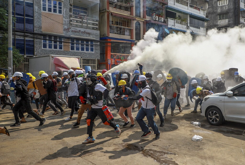 Anti-coup protesters run as one of them discharges a fire extinguisher to counter the impact of tear gas fired by riot policemen in Yangon, Myanmar, W...