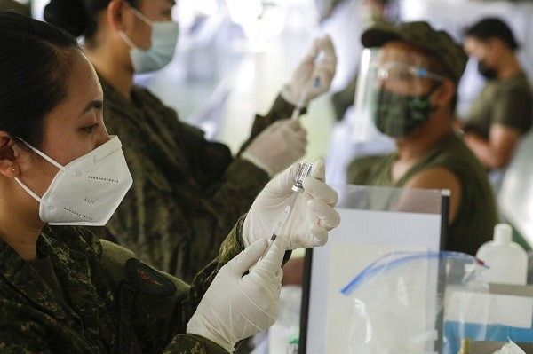 Army doctors prepare to inject China's Sinovac vaccine during start of vaccination at Fort Bonifacio, Metro Manila, Philippines.