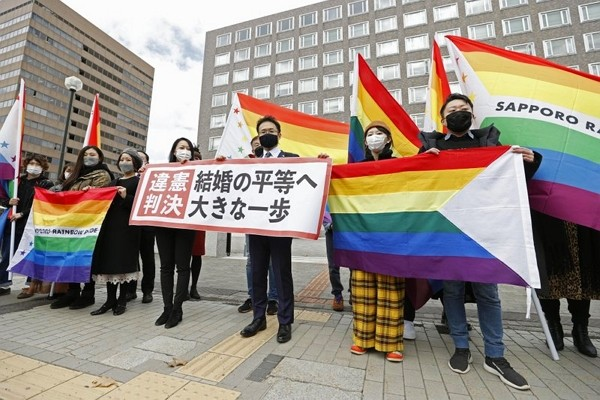 """Plaintiffs' lawyers and supporters hold rainbow flags and a banner that reads: """"Unconstitutional judgment"""" outside Sapporo District Cour..."""