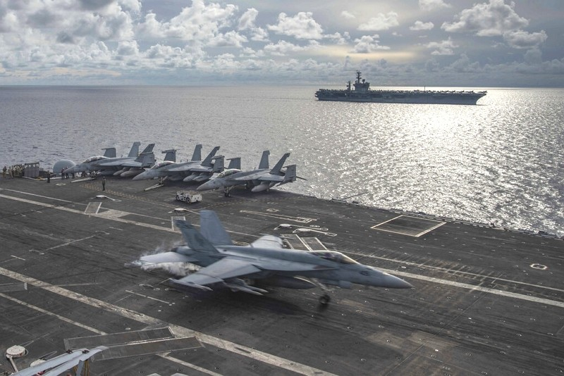 An F/A-18E Super Hornet lands on the flight deck of the USS Ronald Reagan (CVN 76), as USS Nimitz (CVN 68) steams alongside in the South China Sea, Ju...