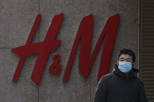 A man wearing a face mask walks by a Swedish fashion brand H&M store outlet in Beijing, Thursday, March 25, 2021.