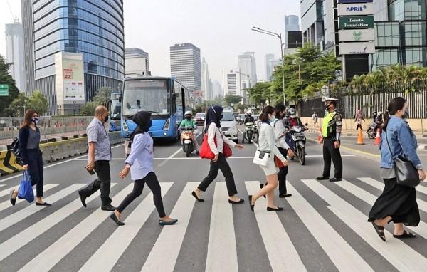 People wearingface masks walk on a pedestrian crossingin Jakarta, Indonesia.