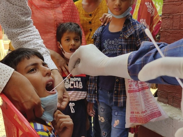 A health worker takes swab sample of children to test for COVID-19 in Prayagraj, India, Thursday, April 8, 2021.