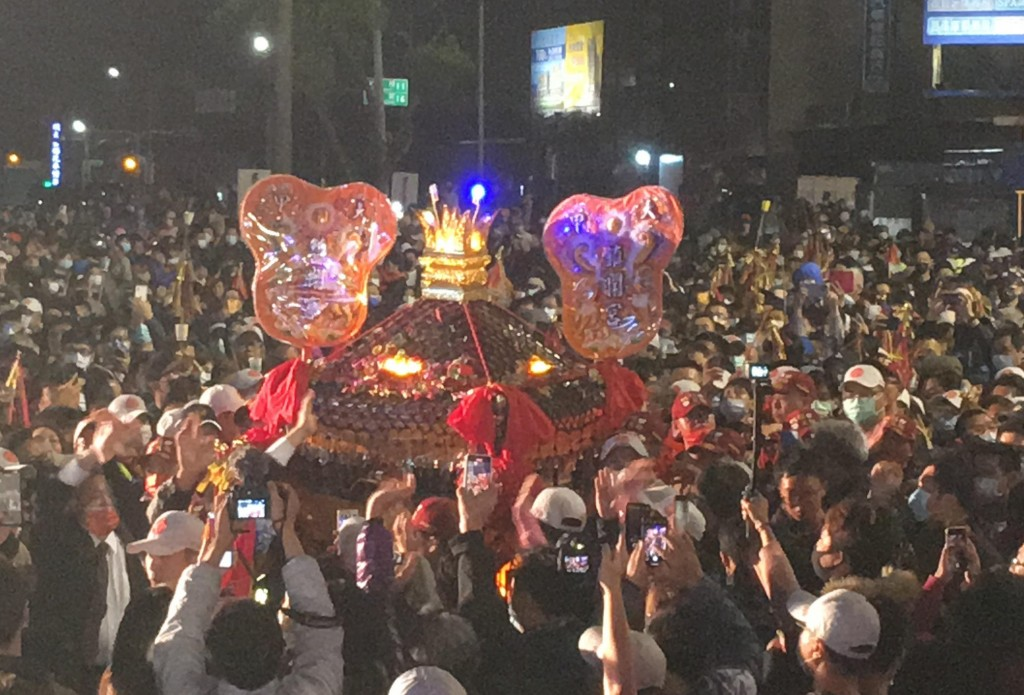 Matsu in her sedan chair being carried through crowd.