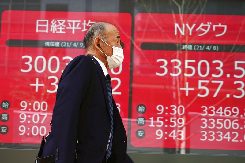 A man walks in front of an electronic stock board showing Japan's Nikkei 225 and New York Dow indexes at a securities firm in Tokyo.