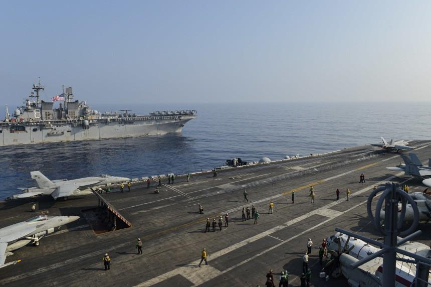 USS Makin Island (background), deck of USS Theodore Roosevelt. (US Navy,Seaman Faith McCollum photo)