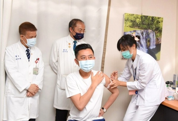 Hsinchu Mayor Lin Chih-chien (center) receives his first shot of AstraZeneca coronavirus vaccine on April 12.