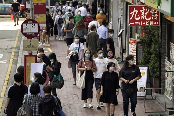 People wearing masks to protect against the coronavirus, walk down a street in Hong Kong.