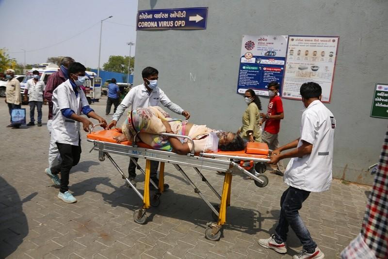 印度醫護人員送COVID-19患者入院(圖/美聯社)