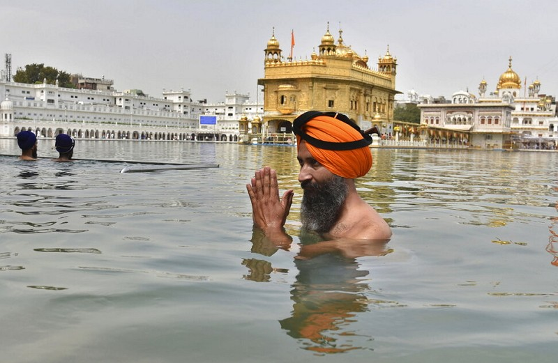 An Indian Sikh offers prayers as he takes a holy dip in the sacred pond at the Golden Temple in Amritsar, India, May 1, 2021.