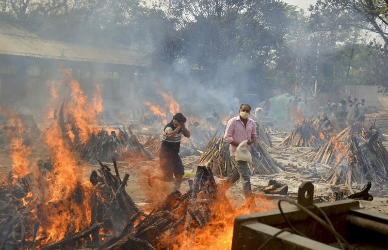 Relatives react to heat emitting from the funeral pyres of COVID-19 victims at a crematorium in the outskirts of New Delhi, April 29, 2021.