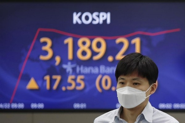 A currency trader walks near a screen showing the Korea Composite Stock Price Index (KOSPI) at the foreign exchange dealing room of the KEB Hana Bank ...