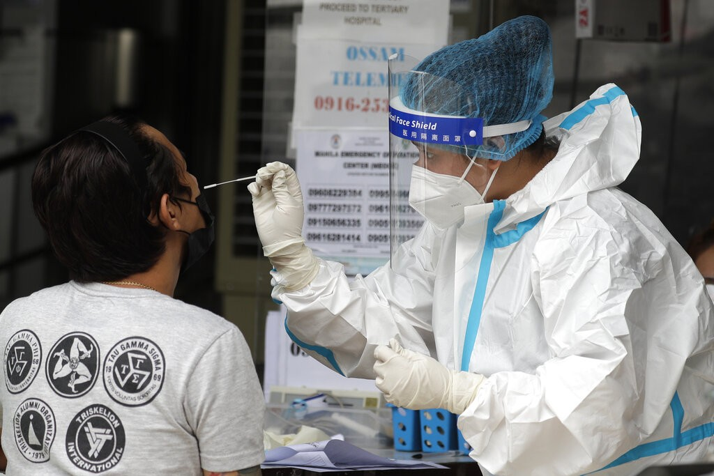 Health worker performs a COVID-19 test on a man at a hospital in Manila, Philippines on Monday, April 26, 2021.
