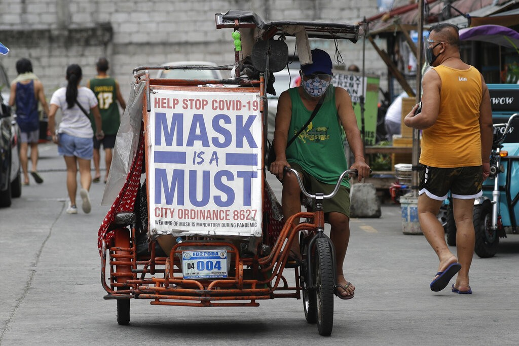 Man rides pedicab withslogan to remind people to wear masks to prevent the spread ofcoronavirus in Manila, Philippines.