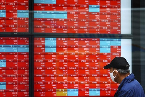 A man wearing a protective mask looks at an electronic stock board showing Japan's Nikkei 225 index at a securities firm.