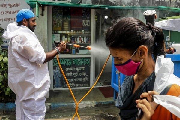 A civic worker sprays sanitizers in front of a shop as a woman wearing face mask walks past in Kolkata, India.