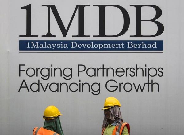 Construction workers chat in front of a billboard for state investment fund 1 Malaysia Development Berhad (1MDB) at the fund's flagship Tun Razak ...