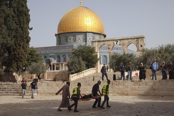 Palestinians evacuate a wounded man during clashes with Israeli security forces in front of the Dome of the Rock Mosque at the Al Aqsa Mosque compound...