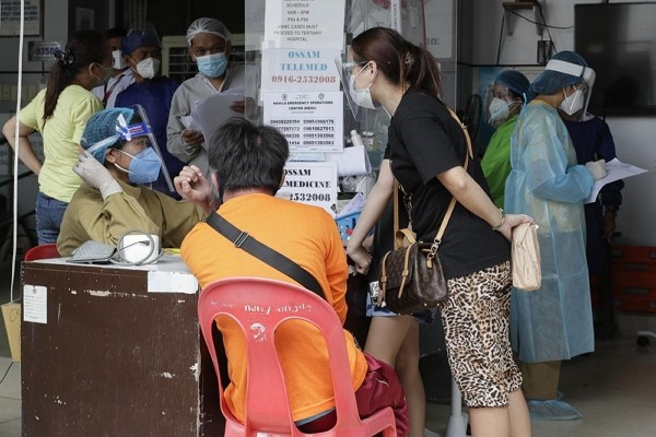 Health workers talk to patients and relatives at a COVID-19 screening area at a hospital in Manila, Philippines.