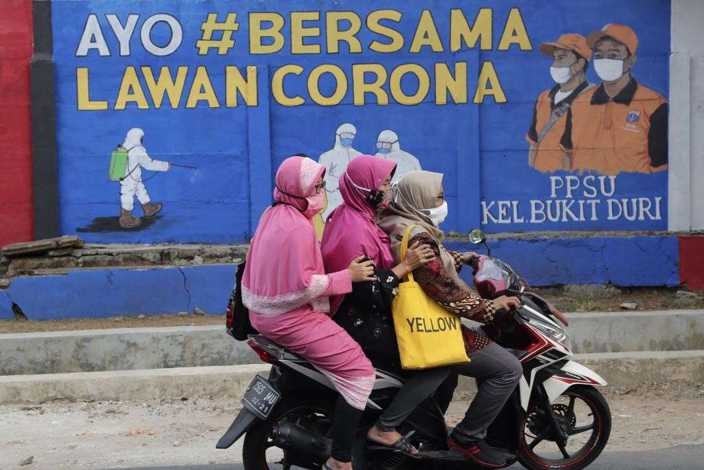 Muslim women riding past a coronavirus poster in Indonesia