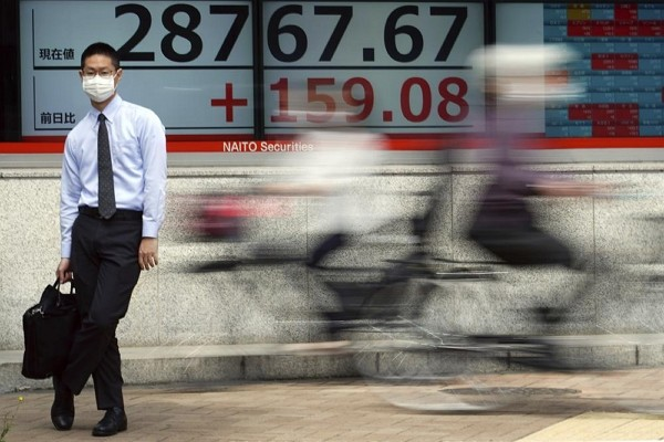 A man wearing a protective mask stands in front of an electronic stock board showing Japan's Nikkei 225 index at a securities firm.