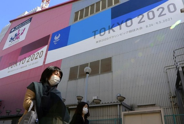 People walk past posters to promote the Olympic Games scheduled to start in the summer in Tokyo.
