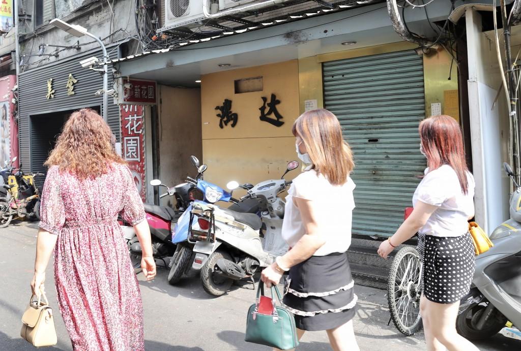 Women walking in front of Hongda Tea House.