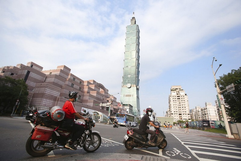 People ride past Taipei 101 after the COVID-19 alert was raised to Level 3 in Taipei, Taiwan, Saturday, May 15, 2021.