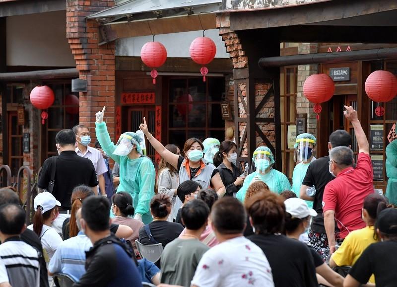 台北市在萬華剝皮寮設置武漢肺炎快篩站,14日下午4時起開始作業,圖為等候篩檢的民眾在廣場上等待叫號。中央社