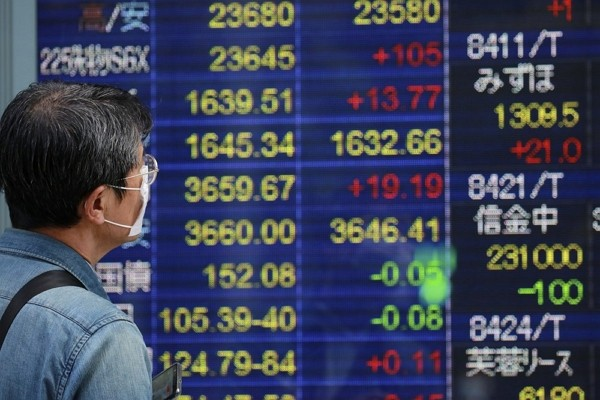 A man looks at an electronic stock board of a securities firm in Tokyo.