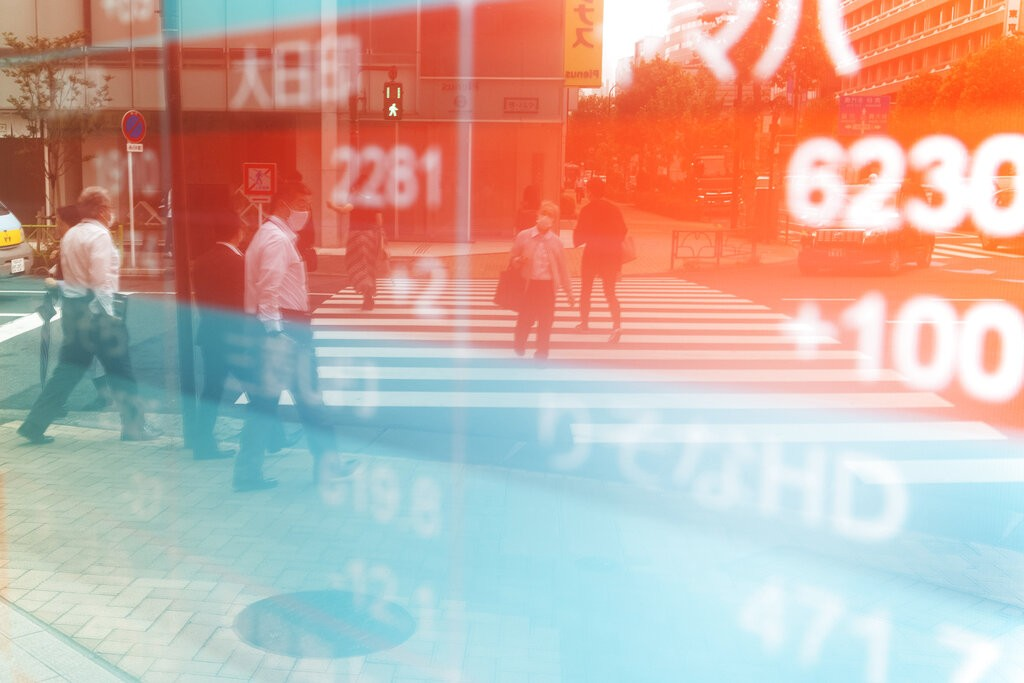 People walk across a traffic intersection in front of a securities firm showing Japan's Nikkei 225 index in Tokyo.